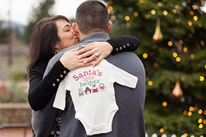 Holding a onsie Christmas pregnancy announcement