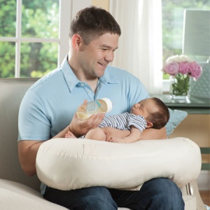 dad using a nursing pillow on baby