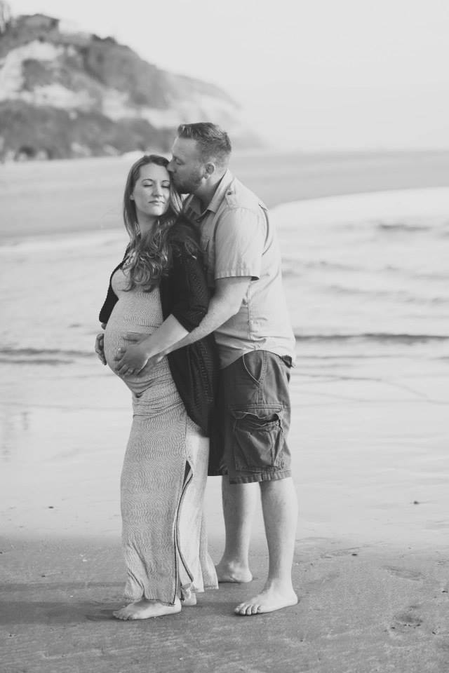 maternity photo shoot at the beach holding wifes belly