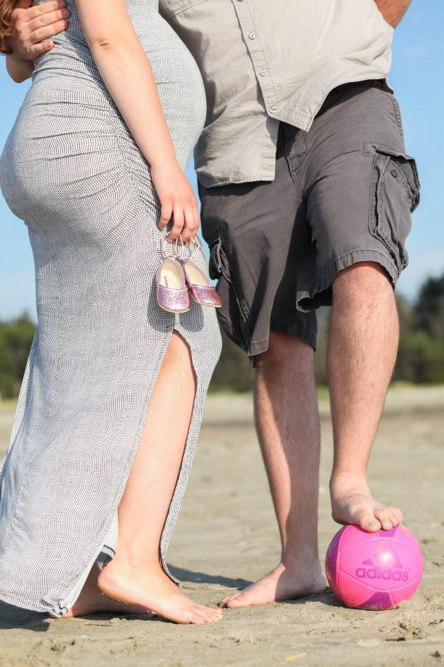 maternity photo shoot at the beach holding shoes stepping on ball
