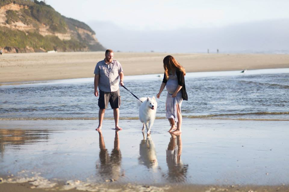 maternity photo shoot at the beach running with dog