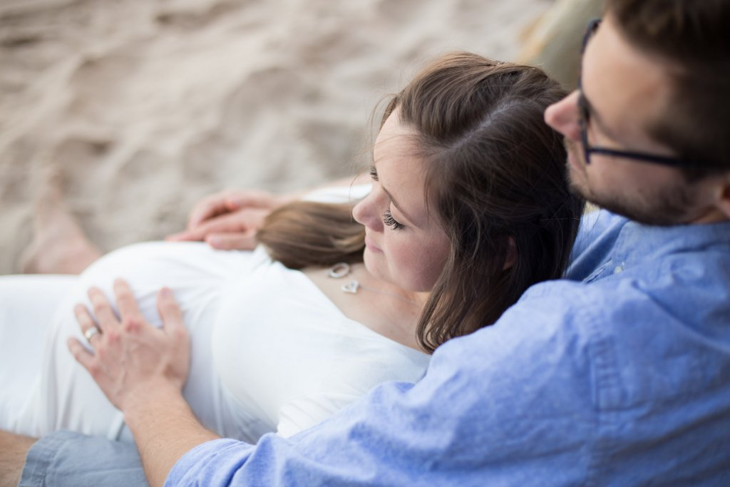 maternity photo shoot at the beach laying down