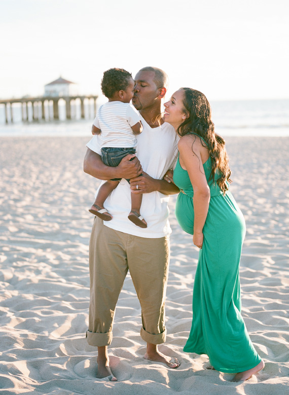 maternity photo shoot at the beach kissing