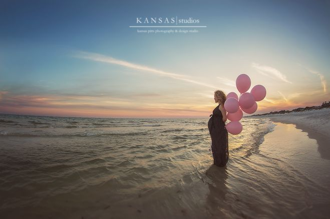 maternity photo shoot at the beach holding balloons