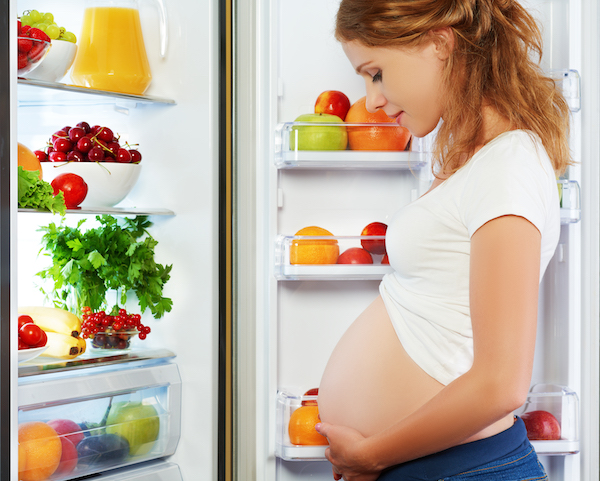 Pregnant woman standing by refrigerator
